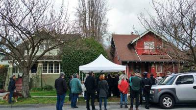 Neighbours at a wake for 4255 W 12th (right), slated for demolition, with media in attendance. The green house next door was built by the same original owner. Photo: Naomi Reichstein